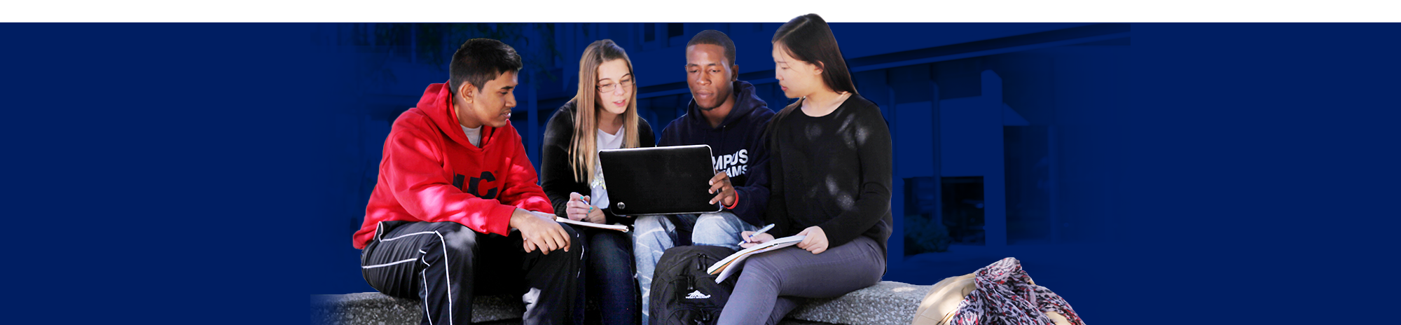 Three students sitting down and huddled around a laptop